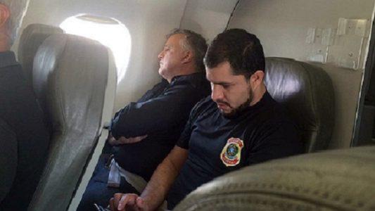 Carlinho Cachoeira é escoltado por agente da PF em voo. (Foto: Internet)